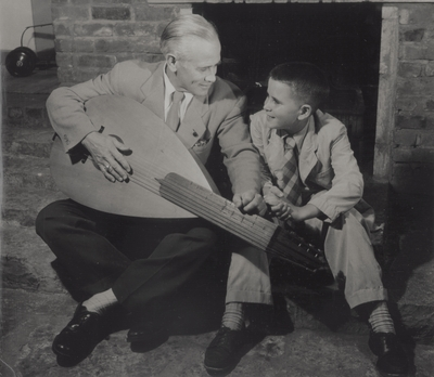 John Jacob Niles with son Tom seated in front of fireplace; Boot Hill Farm; Van Deren Coke