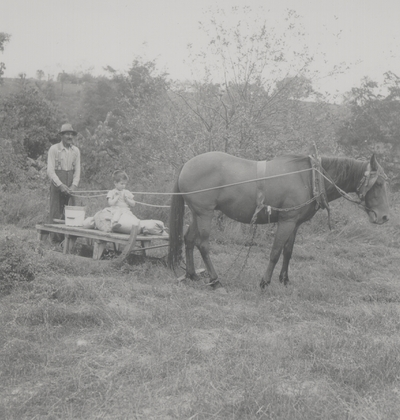 Robert Hicks with John Ed Niles on horse-drawn sled; Boot Hill Farm