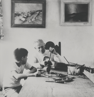 John Jacob Niles repairs a dulcimer while son John Ed looks on in the dining room at Boot Hill Farm; Van Coke
