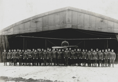 Group of World War I soldiers in front of airplane hangar, John Jacob Niles (front row, far right)