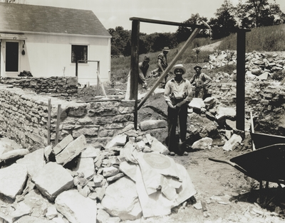 Robert Hicks, foreground, workman on Niles' home.  Background: John Jacob Niles (left) and Claude Snowden (right) and his son; Boot Hill Farm; Kenneth Studio
