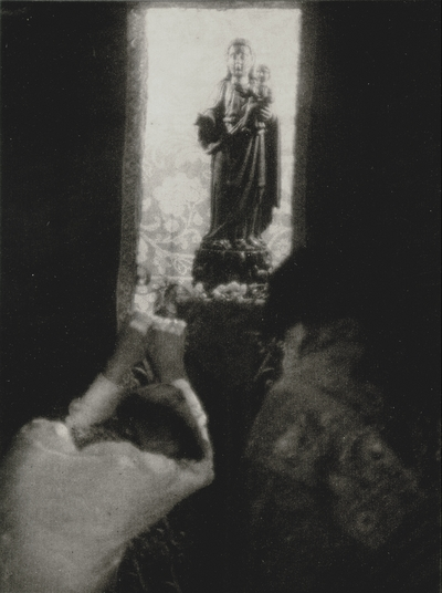 Posed before a statue of the Virgin, John Jacob Niles and Doris Ulmann's maid.  Printed on photo papers, folded and sent as a Christmas card; Doris Ulmann