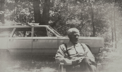 John Jacob Niles sitting in front of station wagon