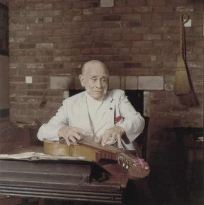 John Jacob Niles performing in front of fireplace; Boot Hill Farm