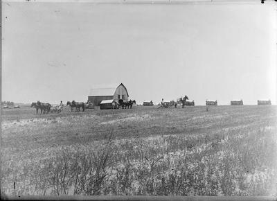 a farm with a barn, horses, and other buildings off in the distance