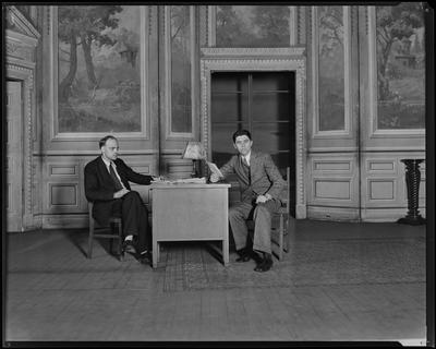 Two men seated at desks in wood-paneled room