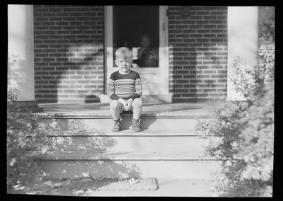 Young boy sitting on porch steps