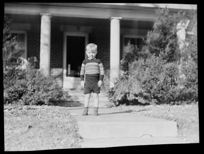 Young boy, standing on sidewalk