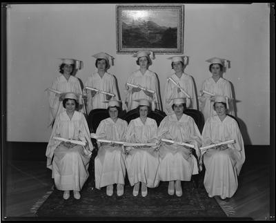 Young women in robes, holding diplomas