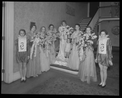 8 young women, child in costumes (beauty pageant?)
