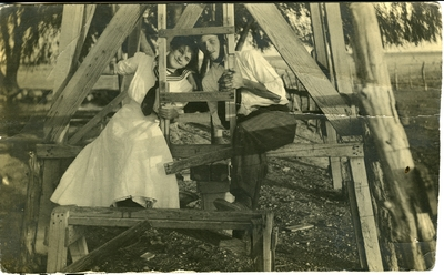 Man and woman sitting at the bottom of a wooden structure  circa 1914
