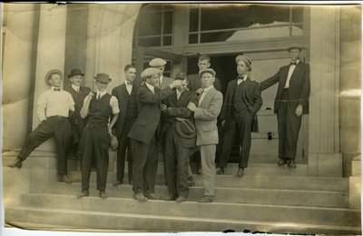 Group of 11 men standing on the steps of a building circa 1914