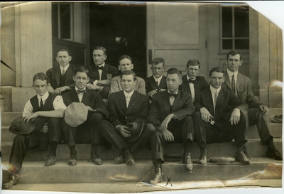 Group of 11 men seated on the steps of a building circa 1914