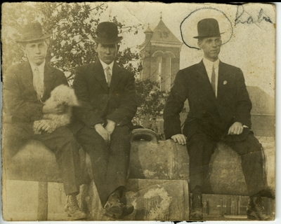 3 men sitting on a cannon on UK's campus circa 1914