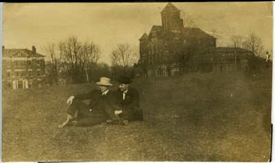 2 men sitting on the lawn of the University of Kentucky's campus with Barker Hall and Buell Armory  in the background circa 1914