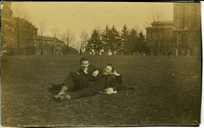 2 men sitting on the lawn of the  University of Kentucky's campus with Barker Hall, Buell Armory and the Administration Building in the background circa 1914