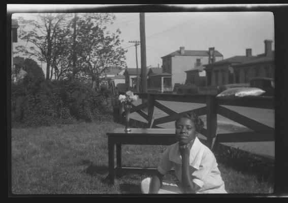 Negative of unidentified woman in yard next to a table with a vase of flowers on it