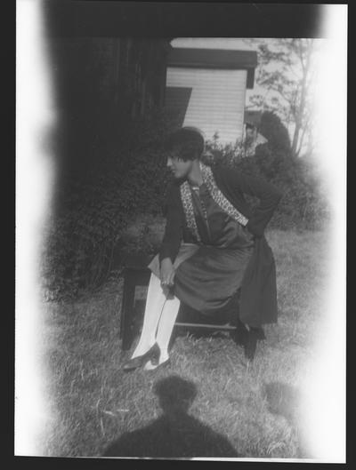 Negative of an unidentified woman sitting on a bench in a yard