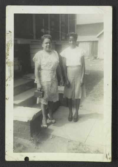 Mrs. Floella B. Harris [L] and an unidentified woman [R] in front of house