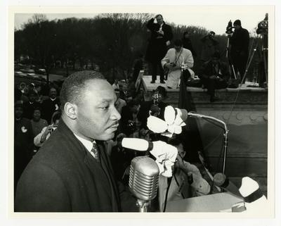 Dr. Martin Luther King, Jr., standing at a podium, photographers and crowd in background