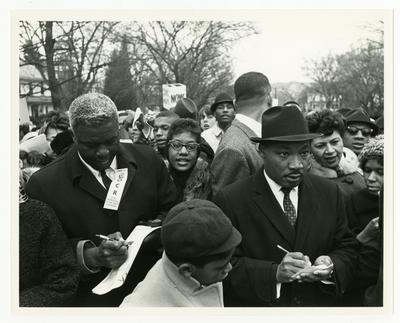 Dr. Martin Luther King, Jr., (right) and Jackie Robinson (left) taking notes during march, Georgia Davis Powers on extreme right over King's shoulder