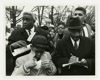 Dr. Martin Luther King, Jr., taking notes during march, Jackie Robinson to his left