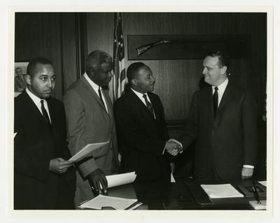 Dr. Martin Luther King, Jr., shaking hands with Kentucky Governor Edward T. Breathitt, Jackie Robinson to King's left, Frank Stanley Jr. to his extreme left