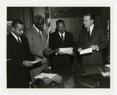 From left to right, Frank Stanley, Jr., Jackie Robinson, Dr. Martin Luther King, Jr., and Kentucky Governor Edward T. Breathitt reading legislative bill to desegregate public accommodations in Kentucky