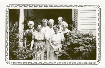Seven unidentified women on porch, handwritten in ink on back