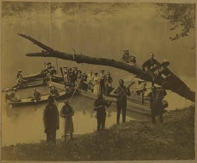 Men and women in boats at the waterside at Boone's Fort with a group of African American male musicians on the shore