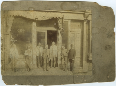 Seven unidentified African American males standing in front of an unidentified building