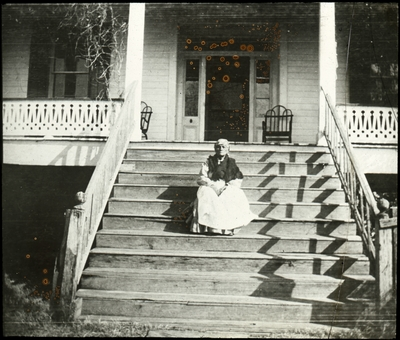 Unidentified African American woman sitting on the front steps of a large house