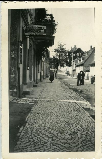 Street with three people.  Sign says Feinbackerei Konditorei