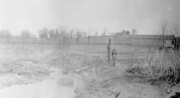 A view of the Right-hand Farm of Grassy Lick Creek taken from the bridge a short distance above the forks of Grassy Lick Creek. The direction is northeast, and the bottom beyond the boy standing by the post is where the 'Grassy Lick' was located in the farms of Grassy Lick Creek