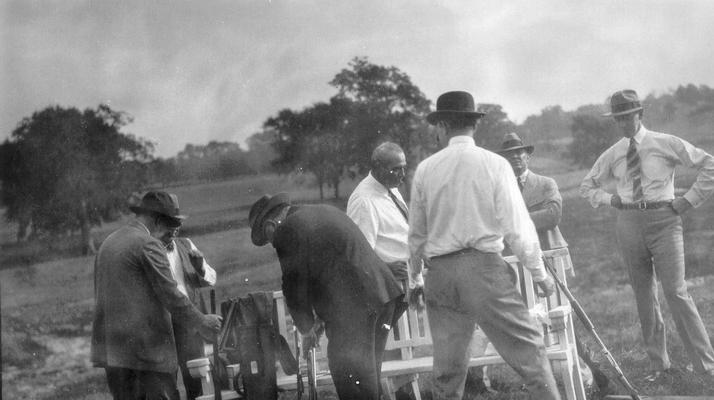 Group of men at a fish fry and shoot, several guns