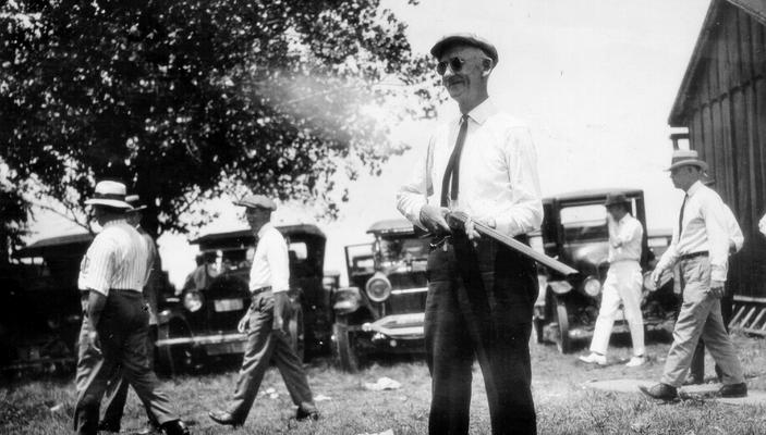 Man with a shotgun, cars and men in background