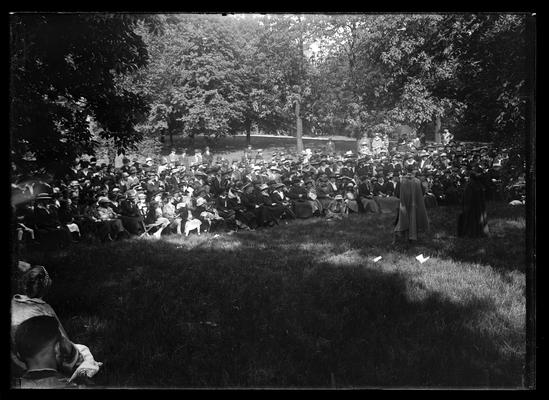 Pageant, crowd assembled on campus under trees, part of the audience