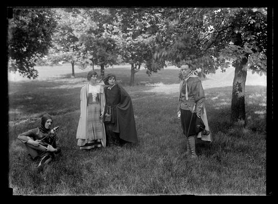 Pageant, play, four actors under trees, court jester to left