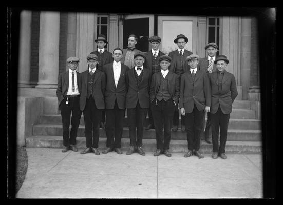 Civil Engineering class standing on steps of Civil Engineering (Pence Hall) building, two without caps
