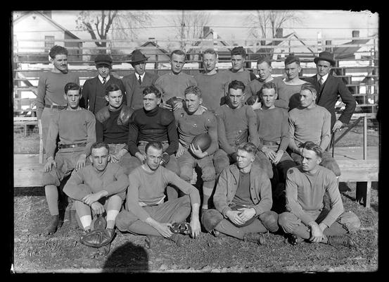 Football squad on bleachers, back left man with mustache and bushy hair