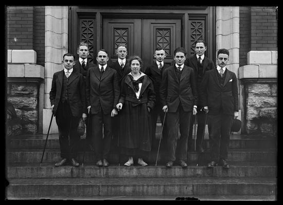 Eight men, one woman, with canes on steps of Carnegie Library