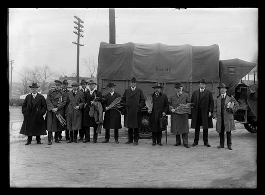 British Commission on Education, group with U.S.Q.M.C. (United States Quartermaster Corps?) truck in background, F. Paul Anderson to left, President F.L. McVey to left of wheel