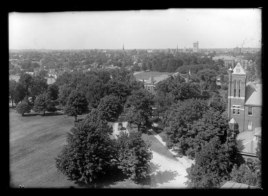 View from Old Main, tower of Barker Hall to right, students in vehicle in driveway (wagon)