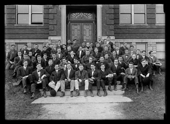Student group, Agricultural Society, men, one woman, in front of Agricultural Building (Scovell Hall), hat on foot of second from left