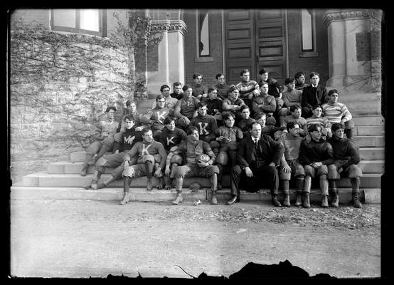 Football squad on steps of Health Building (old Chemistry Building), Coach Fred E. Schacht