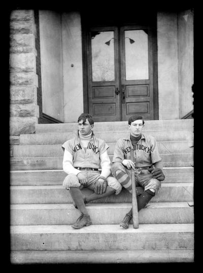 Two baseball players seated on steps