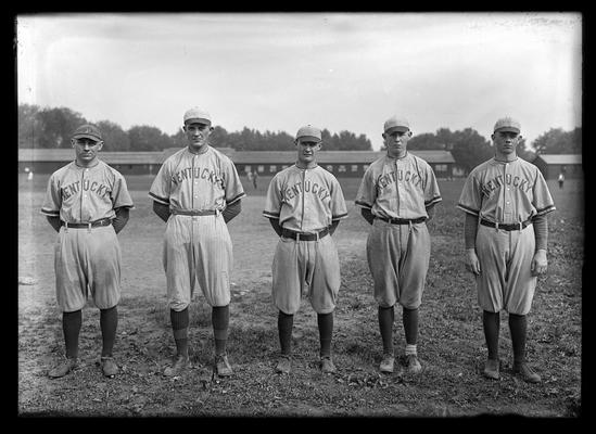 Five baseball players with long, low building in background