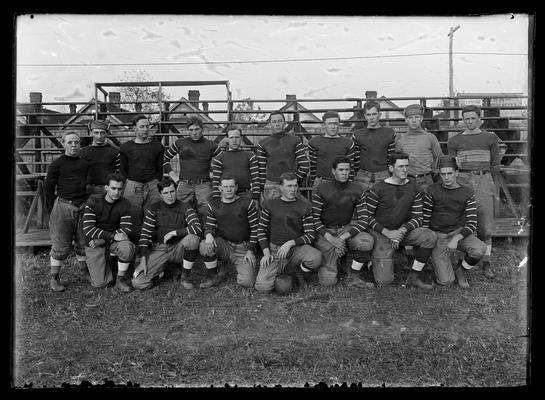 Football team on field, bleachers in background