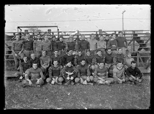 Football squad on field, bleachers in background