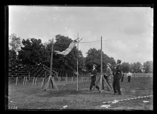 Track meet, pole vault, four men at base of pole